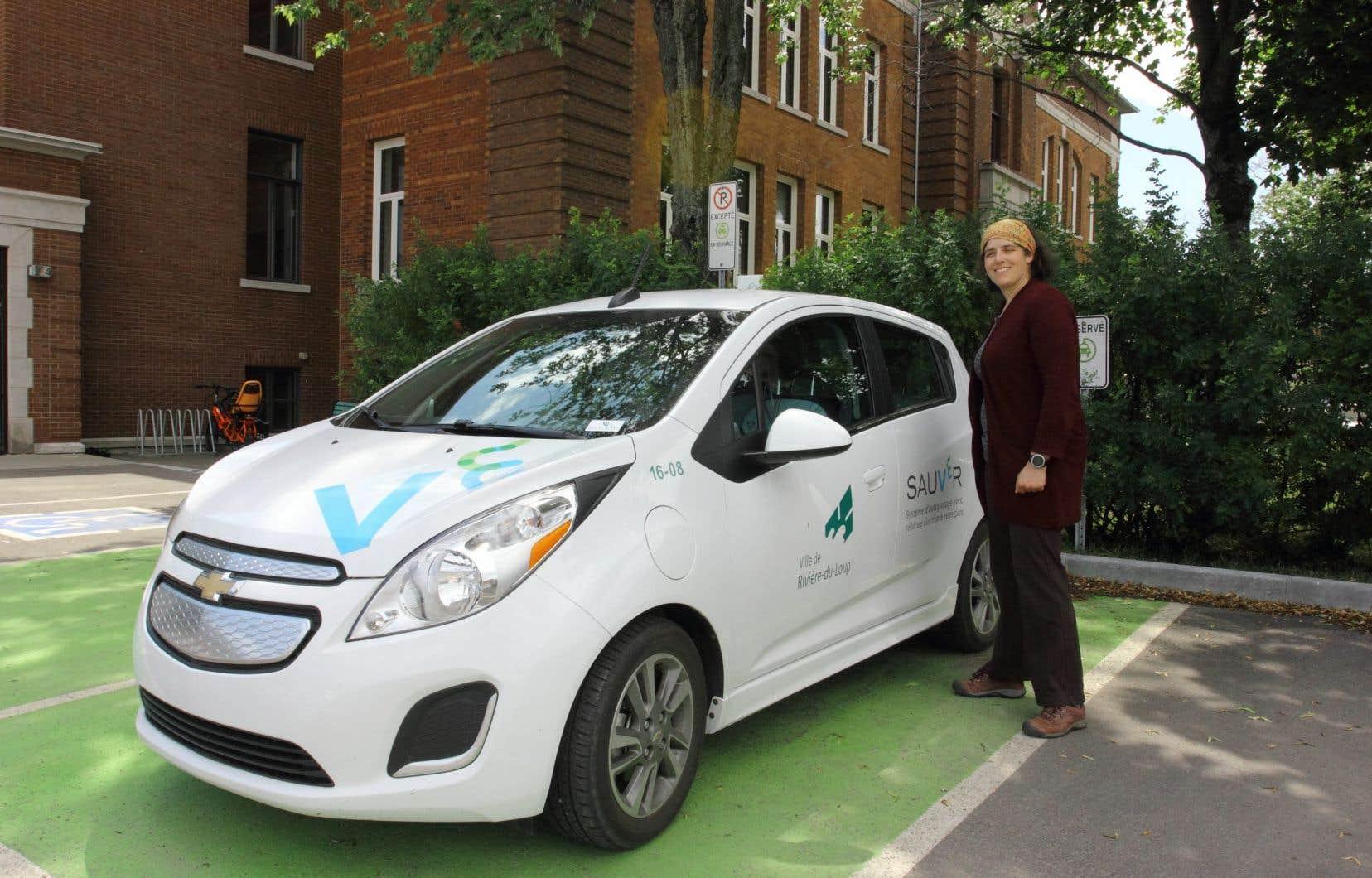 La conseillère en développement durable de Rivière-du-Loup, Marianne Gagnon, devant la Chevrolet Spark en autopartage de la Ville