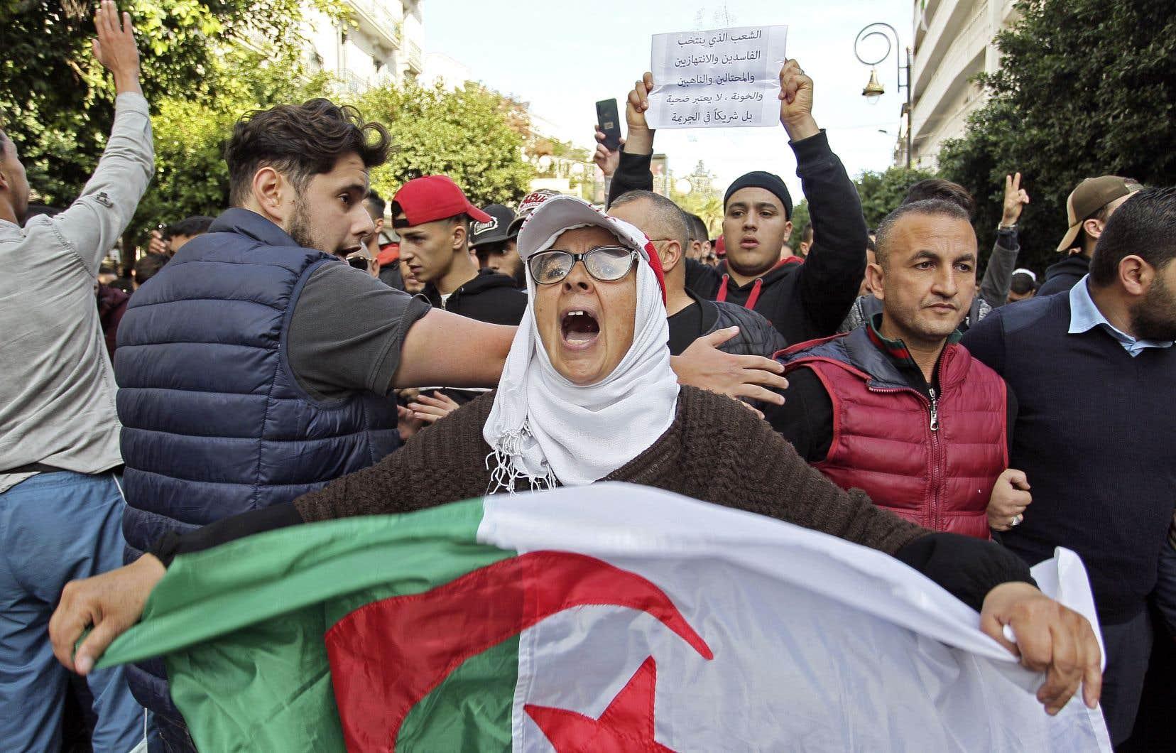 Une femme a pris part à une manifestation antigouvernementale en tendant un drapeau algérien et en criant des slogans à Alger, jeudi.