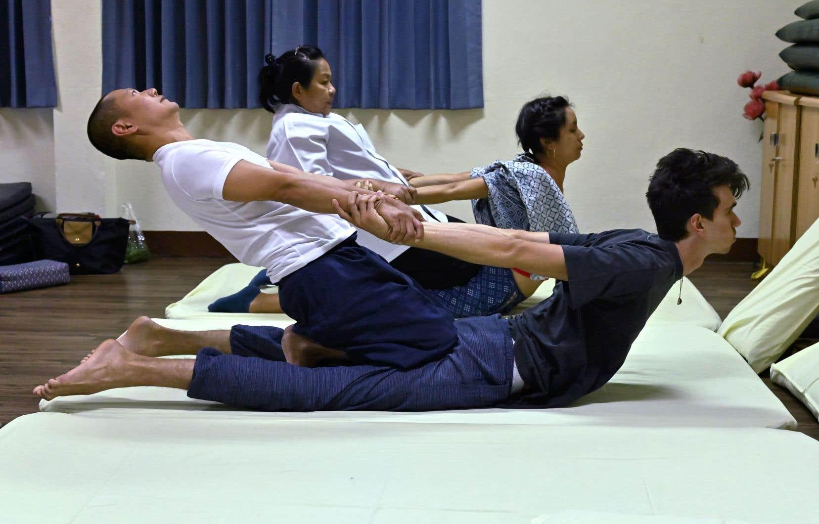 Sari, une masseuse chilienne (au fond), est venue spécialement à l'école du temple du Bouddha couché de Bangkok pour perfectionner sa maîtrise du Nuad, le massage thaï à l'histoire millénaire.