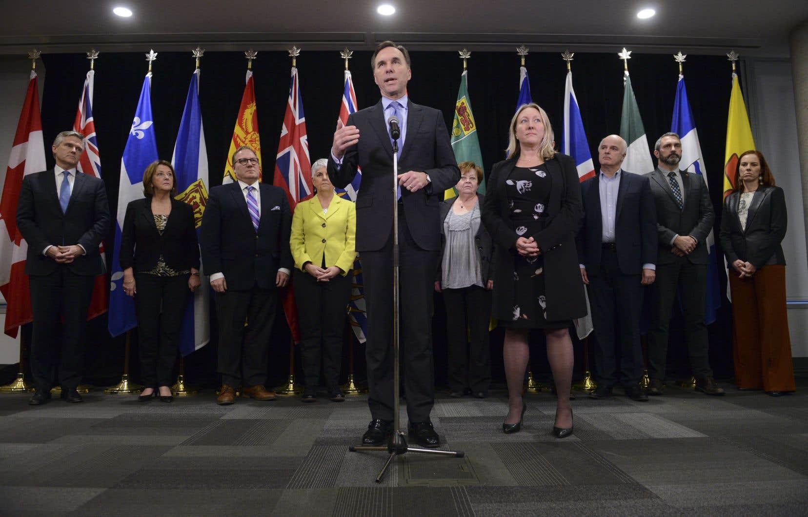 Le ministre fédéral des Finances, Bill Morneau (au centre) accompagné de ses homologues des provinces et territoires après la rencontre de mardi.