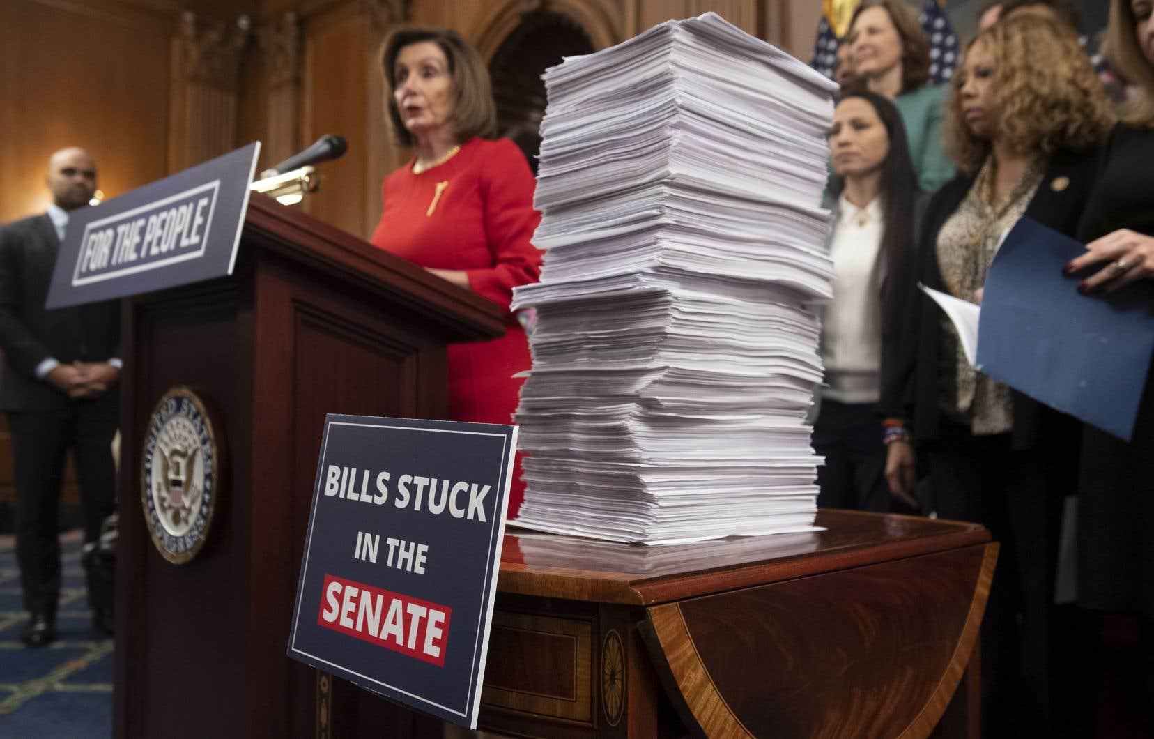 La cheffe démocrate Nancy Pelosi a empilé en conférence de presse, jeudi, les copies de projets de loi en attente d'approbation par le Sénat contrôlé par les républicains.