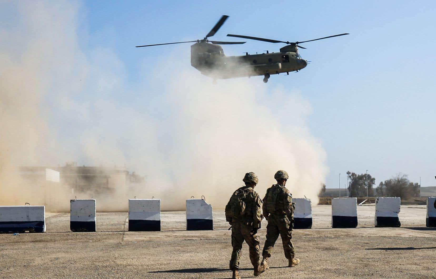 Des troupes américaines marchent alors qu'un hélicoptère C-47 Chinook américain survole le village d'Oreij, au sud de Mossoul, en février 2017.