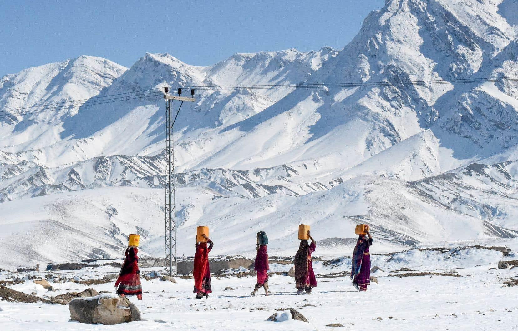 Des résidents de la région de Khanozai, au Pakistan, portent des sceaux d'eau jusqu'à leur domicileaprès de fortes chutes de neige.