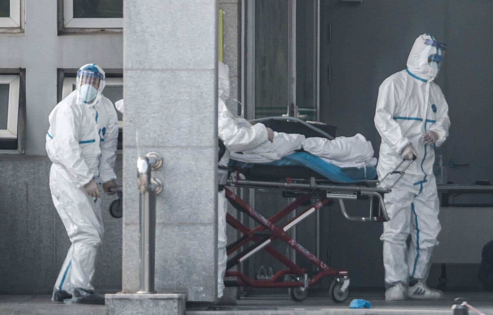 Des membres du personnel médical transportent un patient à l'hôpital de Jinyintan, où des patients infectés par un mystérieux virus semblable au SRAS sont traités, à Wuhan, dans la province centrale du Hubei en Chine, le 18 janvier 2020.