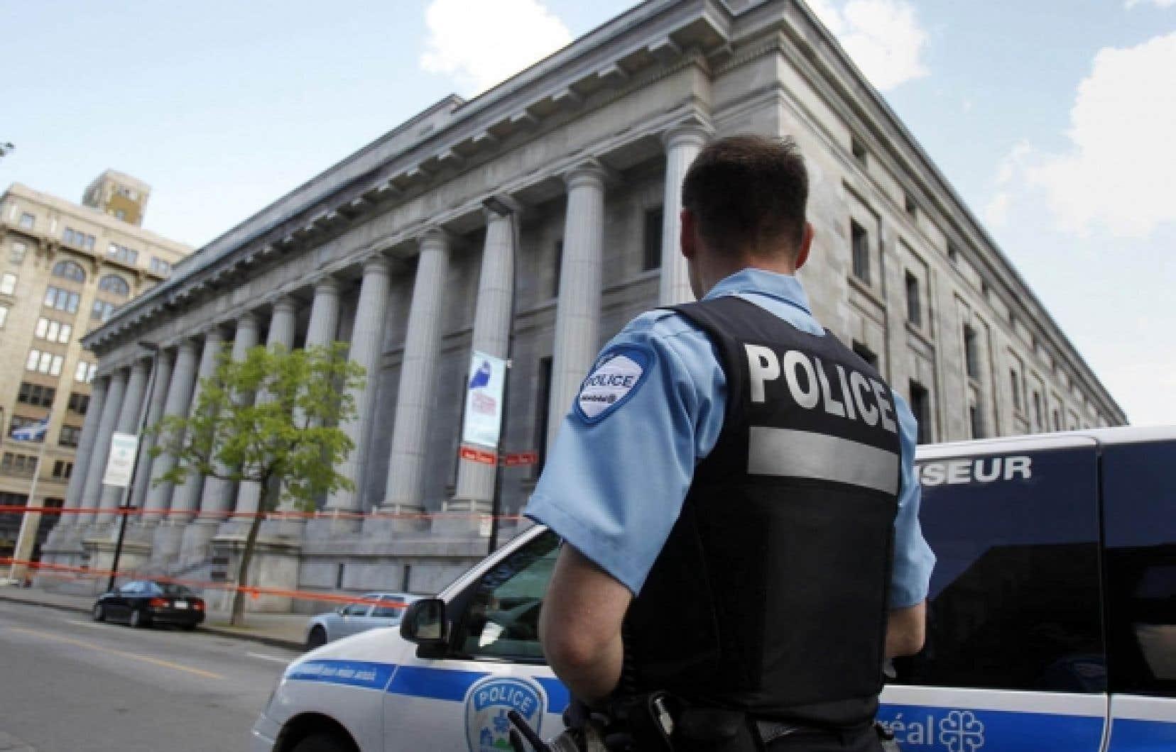 Depuis 35 ans, les dossiers traités par les tribunaux se sont complexifiés, et les formes de la criminalité se sont diversifiées, appelant une modernisation de l'institution juridique. Ci-dessus, un policier devant le palais de justice de Montréal. <br />