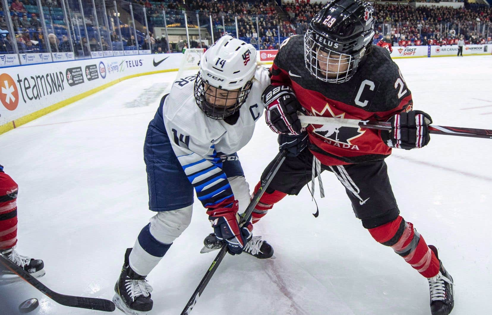 L'Américaine Brianna Decker et la Québécoise Marie-Philip Poulin bataillant pour la rondelle lors du tournoi des Quatre Nations en novembre 2018.
