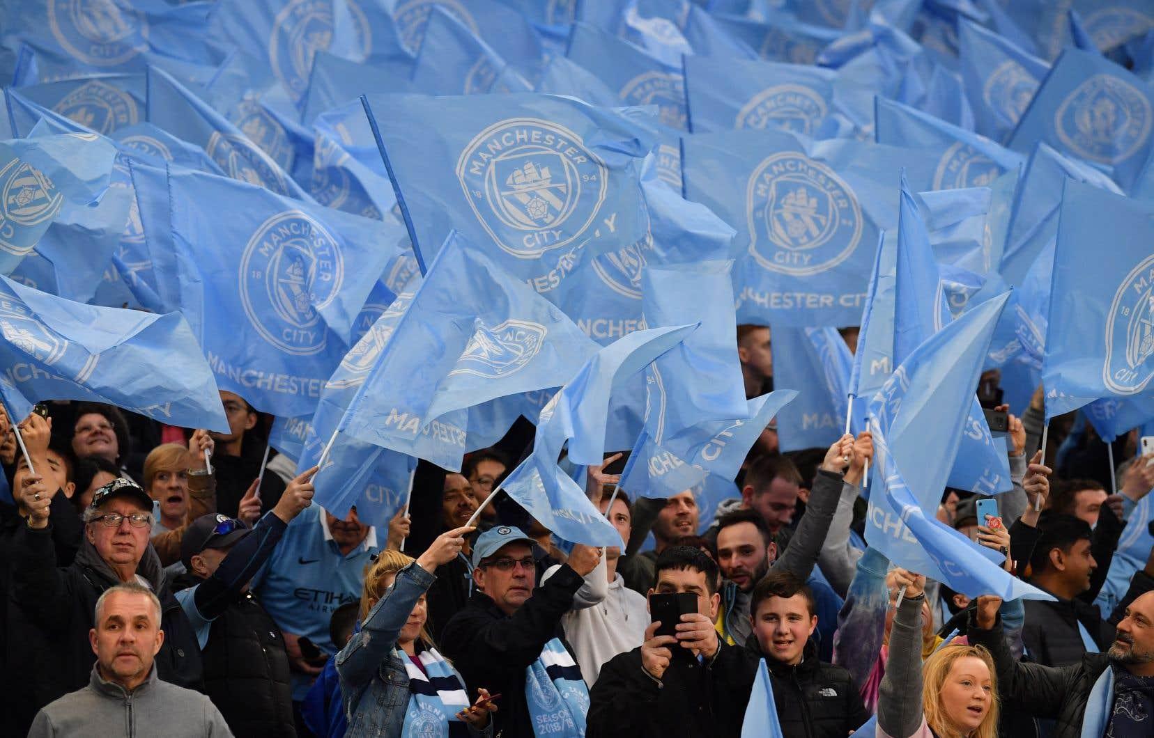 Des partisans de Manchester agitent des drapeaux lors d'un match de football au stade Etihad, en 2019.