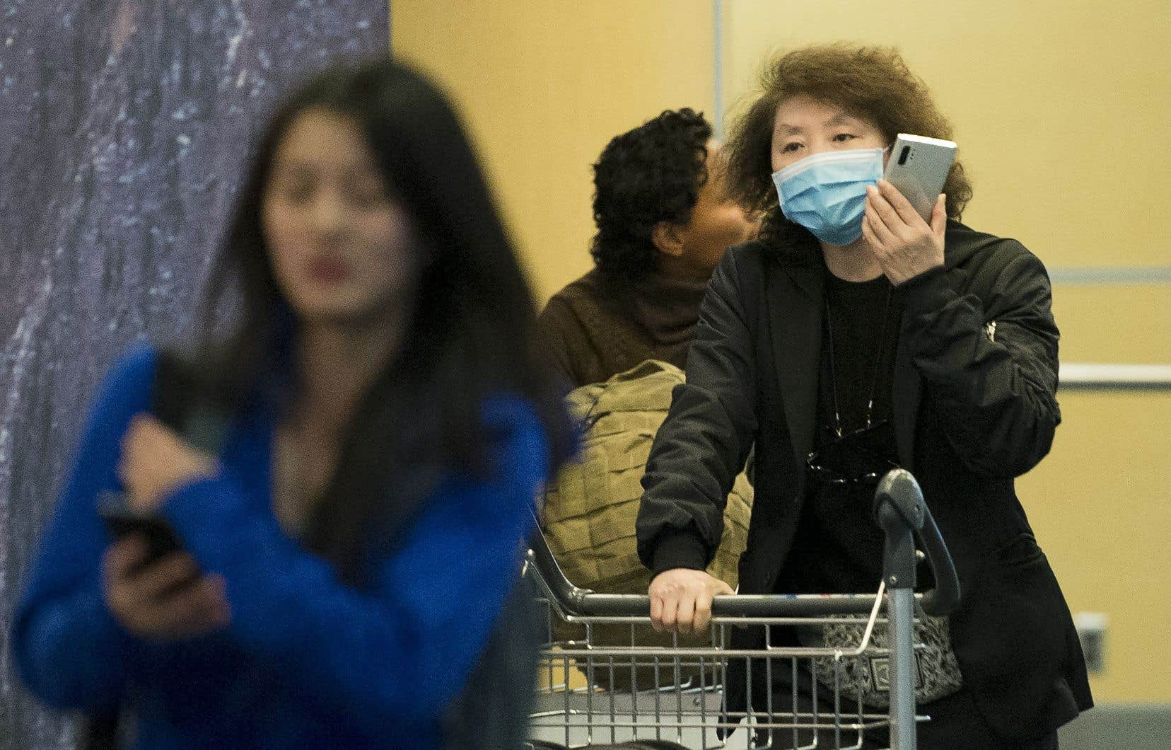 Une voyageuse porte un masque dans la zone des arrivées internationales à l'aéroport international de Vancouver à Richmond, en Colombie-Britannique, le jeudi 23 janvier 2020.