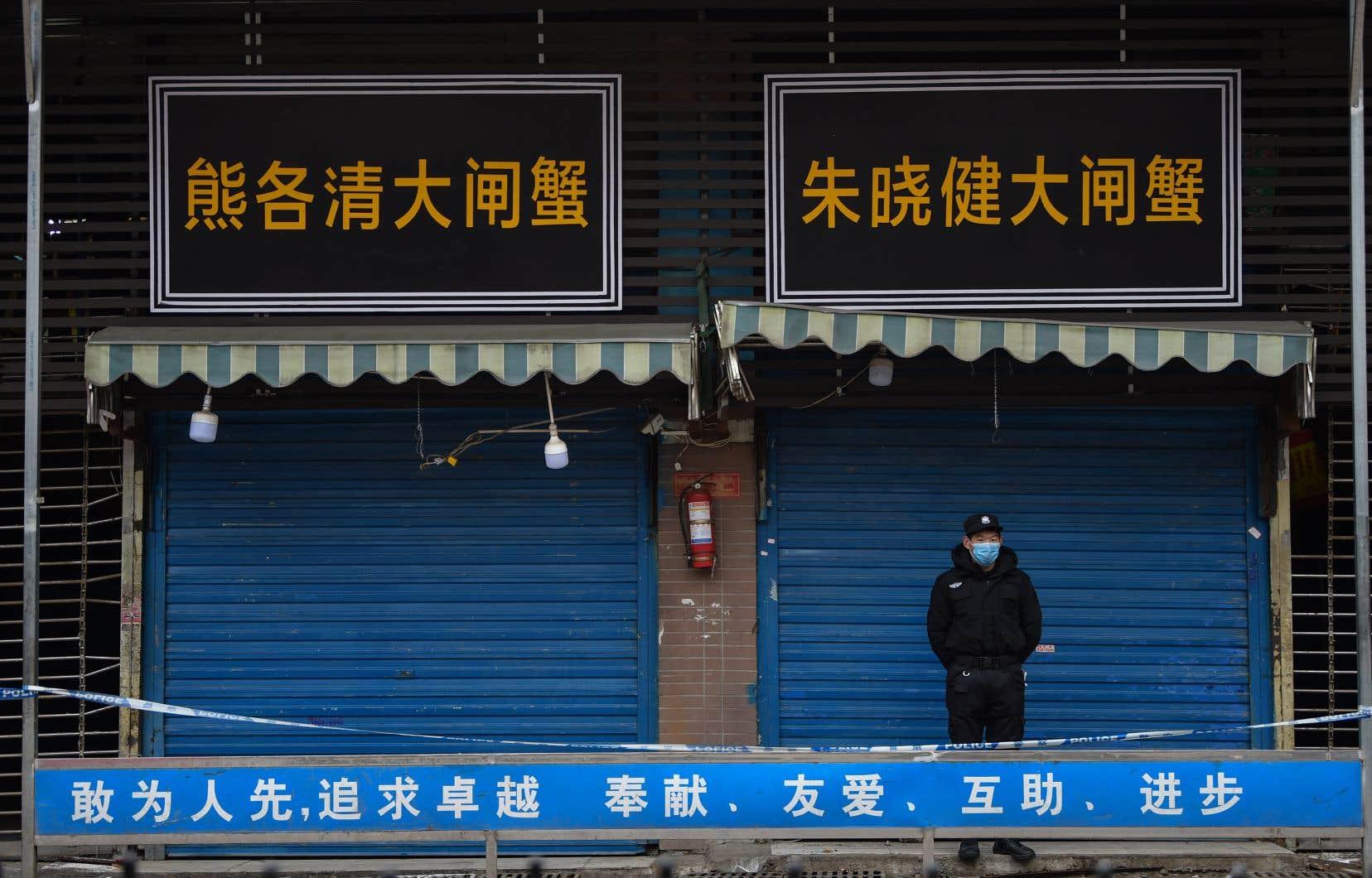Un gardien de sécurité surveille l'extérieur du marché Huanan Seafood où le coronavirus a été détecté à Wuhan, en Chine.