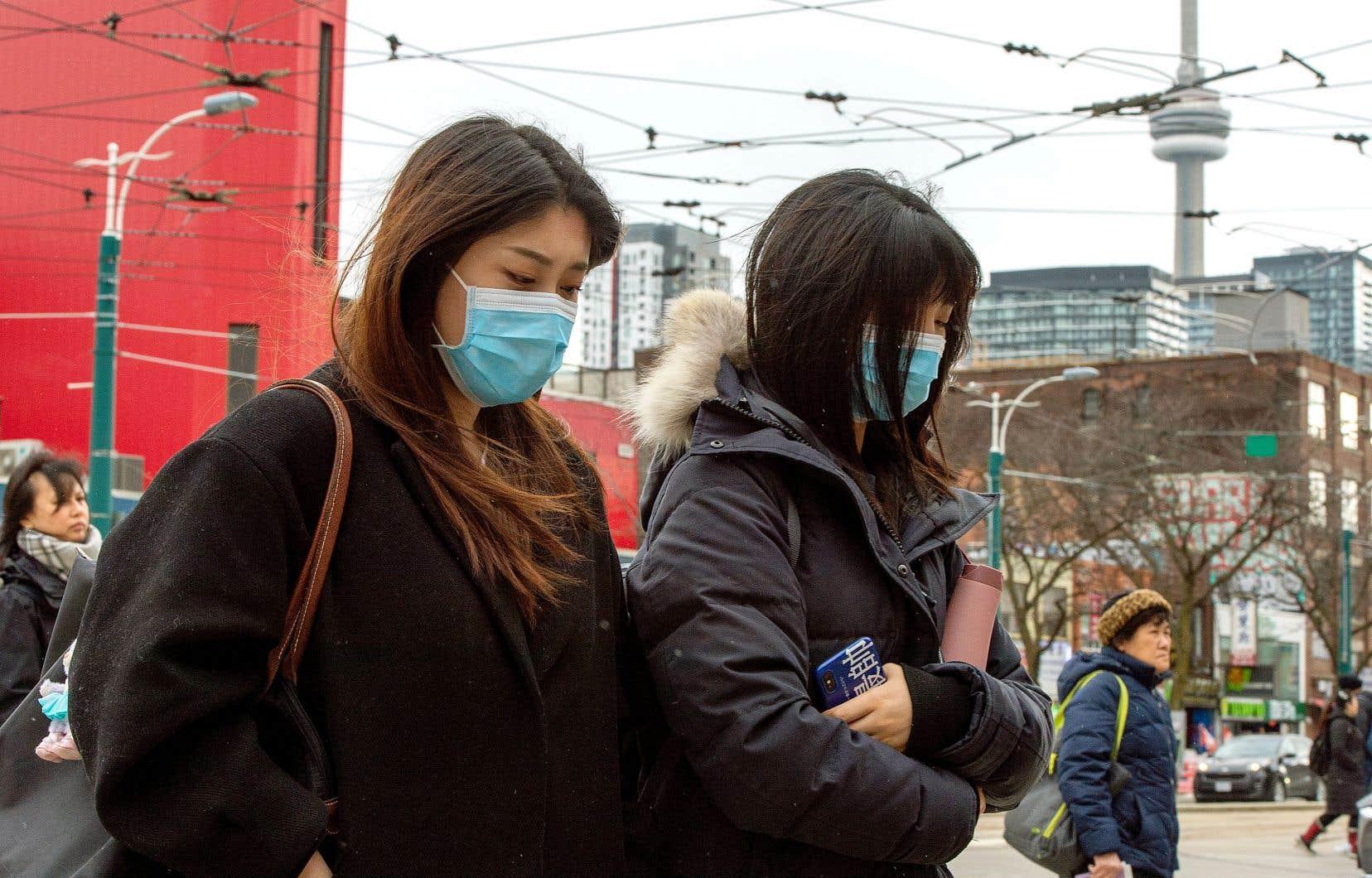 Les autorités sanitaires du Canada ont confirmé qu'à Toronto, un homme arrivant de Chine a été contaminé par le coronavirus. Un test préliminaire réalisé sur sa conjointe, qui était du voyage, s'est révélé positif. Sur notre photo, deux personnes d'origine asiatique marchent au centre-ville de Toronto.