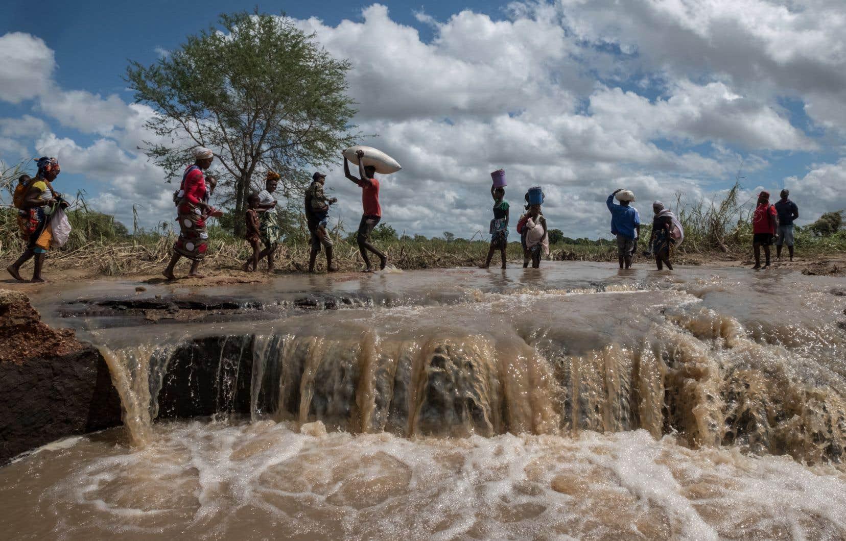 Un groupe d'habitants du Mozambique marche les pieds dans l'eau sur la route qui mène de Pemba à Metuje, inondée après le passage du cyclone Kenneth en avril 2019.