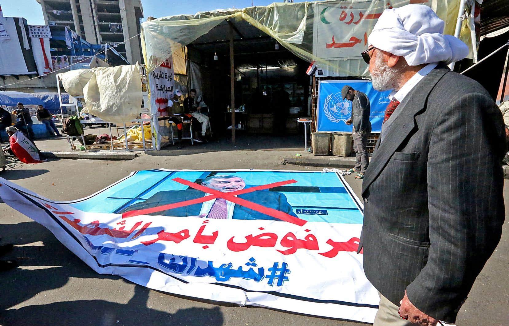 Une affiche vandalisée du premier ministre désigné, Mohammed Allawi, a été déposée sur la place Tahrir, à Bagdad, lundi.