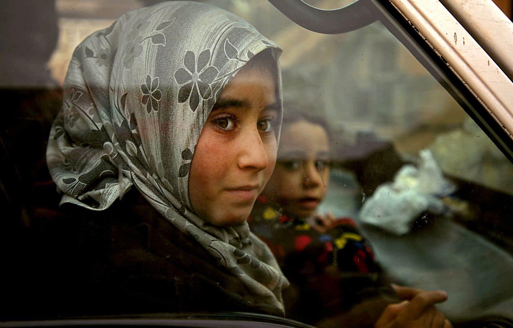 Deux jeunes filles photographiées à travers la vitre d'une voiture, à Hazano, dans le nord-est de la Syrie, fuyant les combats