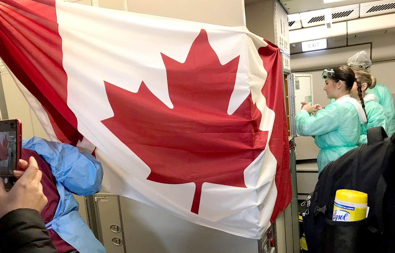 Des passagers ont dressé un drapeau canadien dans l'avion nolisé à bord duquel ils ont quitté la Chine, jeudi, pour revenir au Canada.