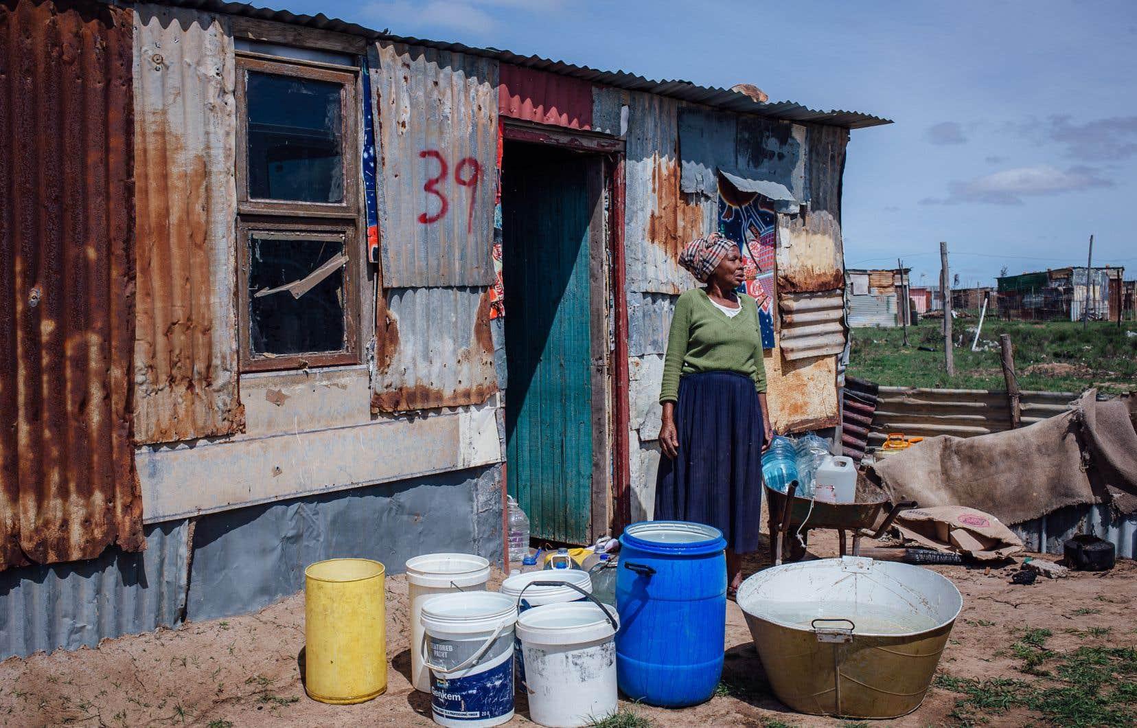Grandma, une habitante du bidonville de Nkanin, en périphérie de Makhanda, entourée de tous les contenants d'eau potable qu'elle a pu réunir.