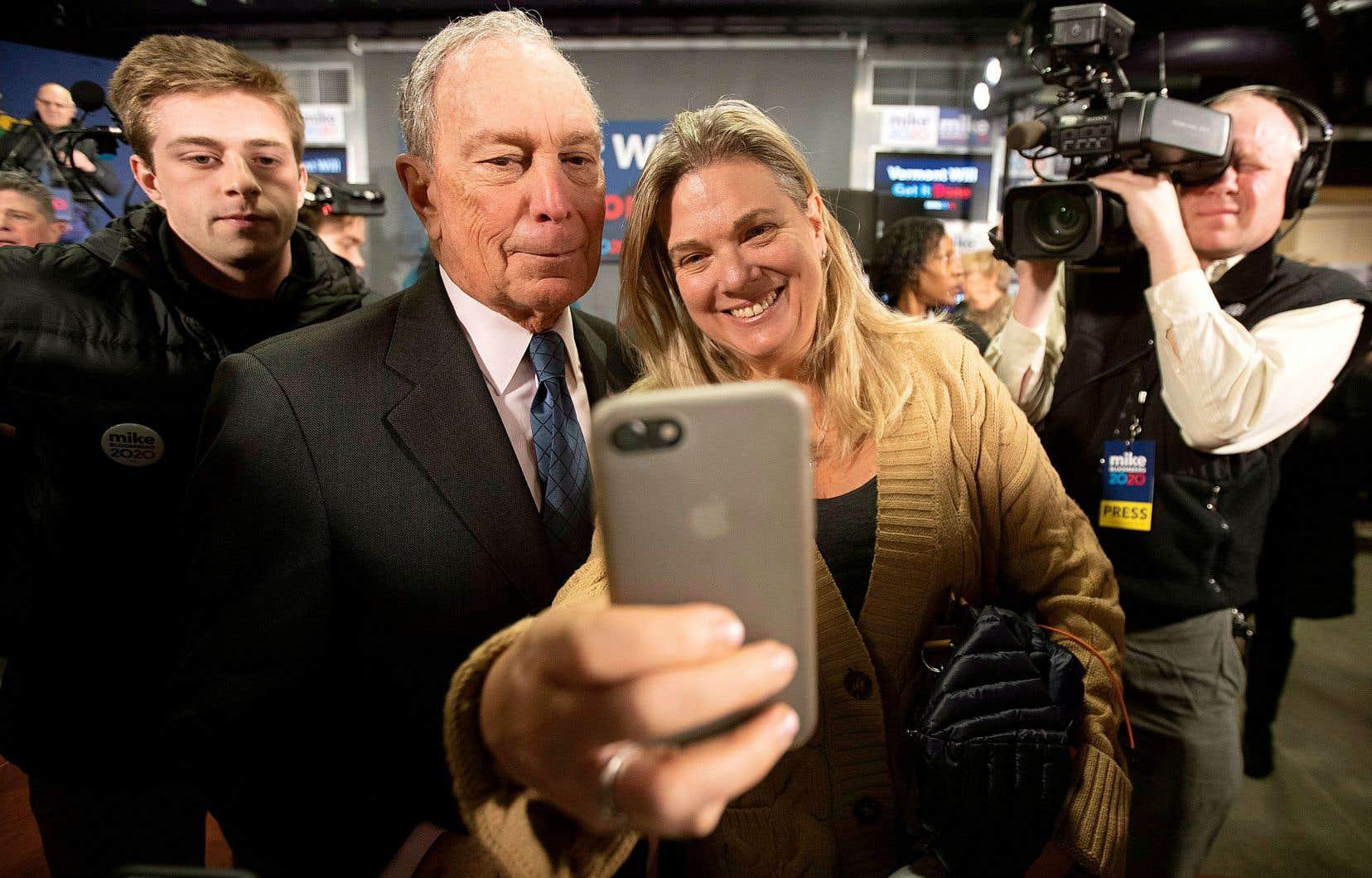 Michael Bloomberg, photographié fin janvier avec une partisane à Burlington, au Vermont, arrive en deuxième place d'un nouveau sondage publié mardi.