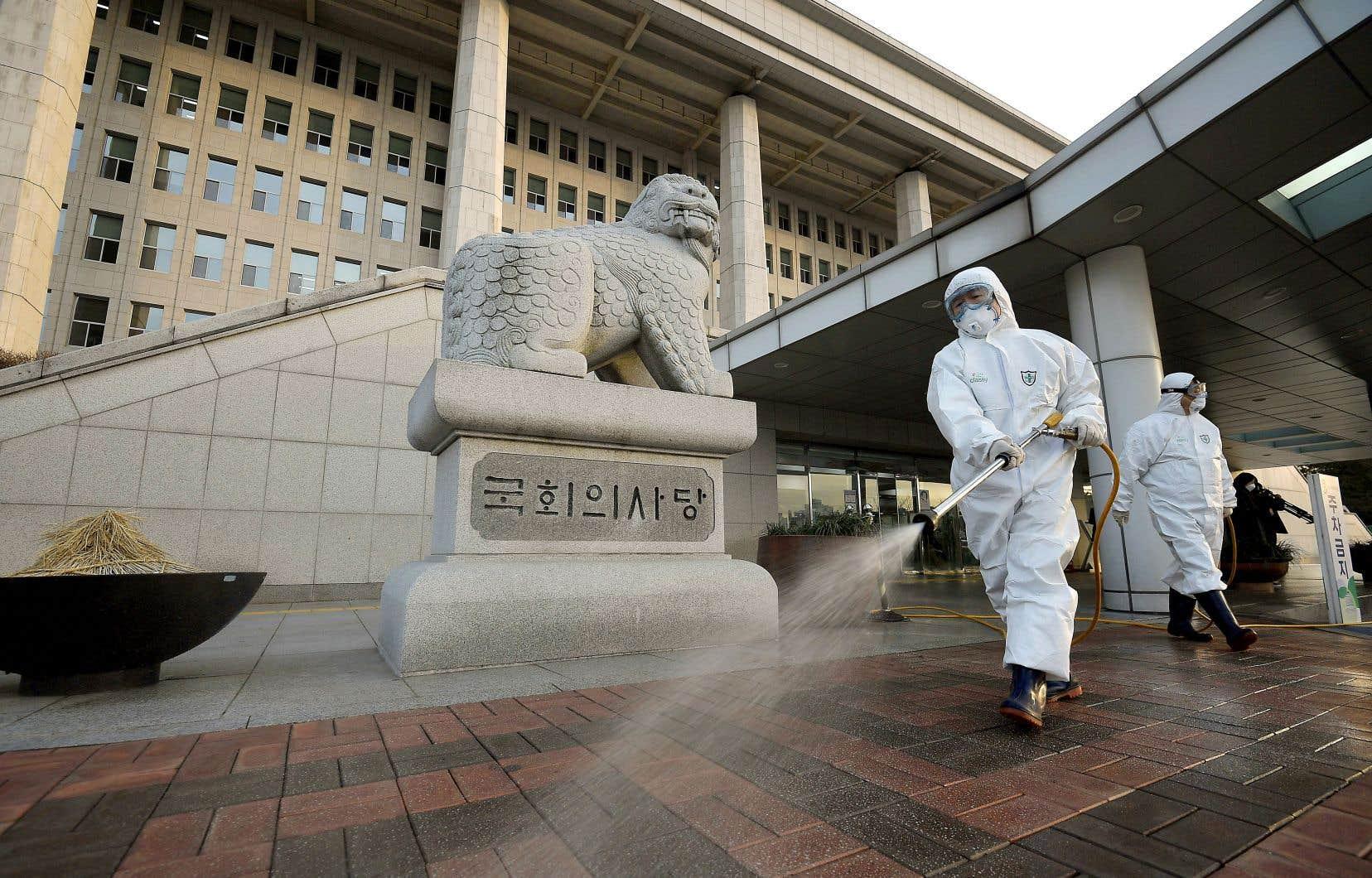 En Corée du Sud, un total de 893 cas de COVID-19 a jusqu'à présent été répertorié, dont huit décès. Lundi, des travailleurs portant des combinaisons et des masques de protection pulvérisaient des matières désinfectantes à proximité de l'Assemblée nationale, à Séoul.