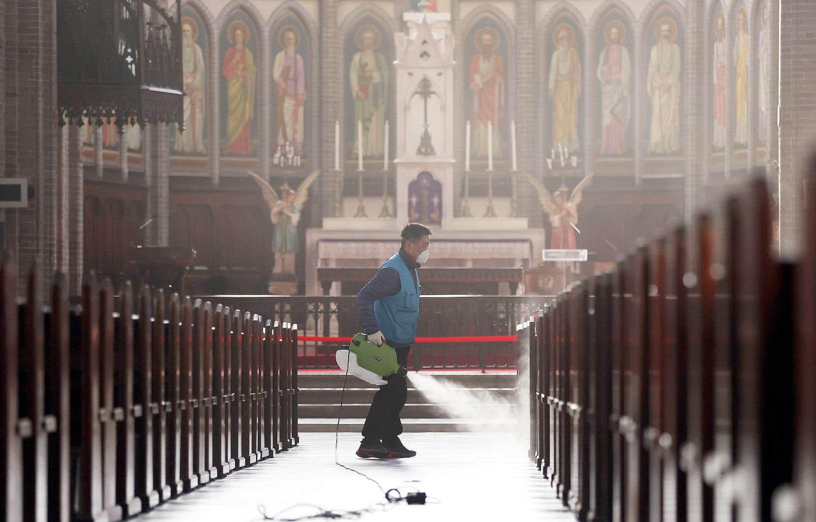 Un homme désinfectait les bancs de la cathédrale de Myeongdong, à Séoul, mercredi. La Corée du Sud reste le premier foyer de contamination après la Chine, avec près de 1600 cas répertoriés.