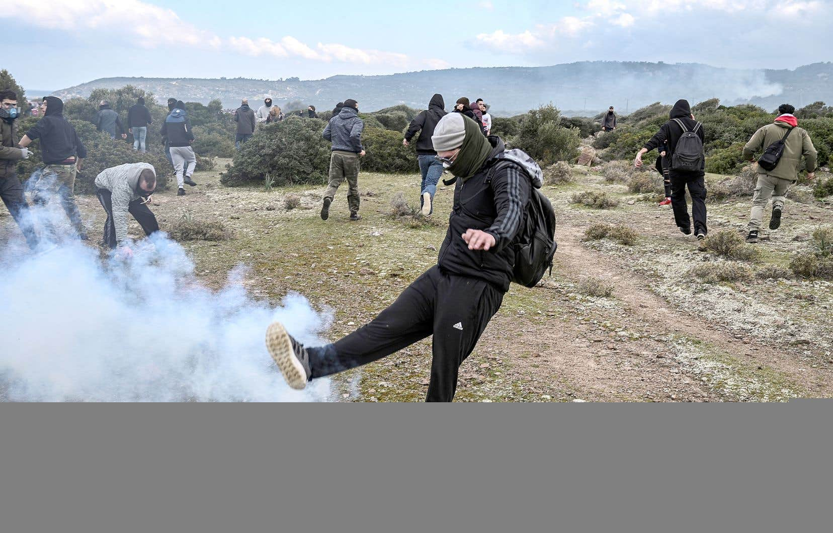 Un homme repoussant du pied une bonbonne de gaz lacrymogène, lors d'une manifestation contre les nouveaux camps de migrants à proximité du village de Mantamados, mercredi