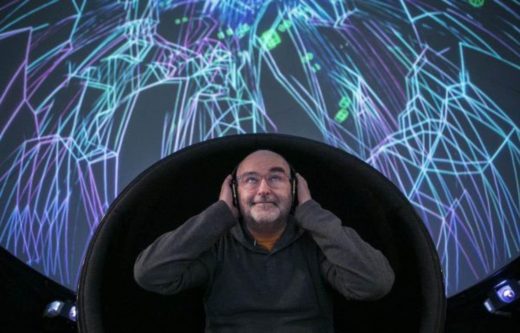 Alain Brunet sous l'un des dômes à la Société des arts technologiques de Montréal, avec des effets lumineux projetés à l'intérieur.