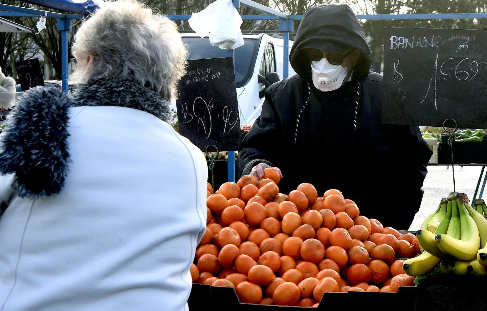 La France est devenue un nouveau foyer aigu de la contamination en Europe. Sur la photo, un homme portant un masque au marché public de Crépy-en-Valois
