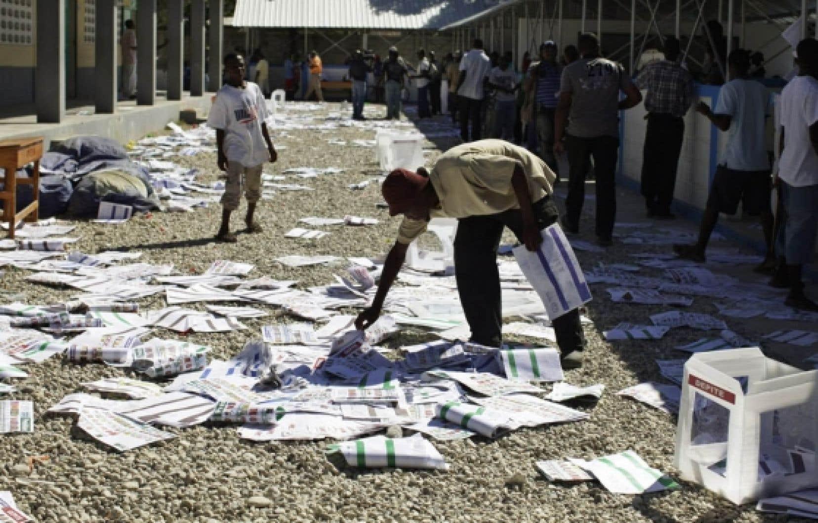 Un homme ramasse des bulletins de vote après que des électeurs, mécontents de ne pas trouver leurs noms sur les listes, eurent saccagé un centre de vote à Port-au-Prince, hier, jour d'élections législatives et présidentielle. Le scrutin a été annulé dans 56 des 1500 bureaux de vote en raison de violences.<br />