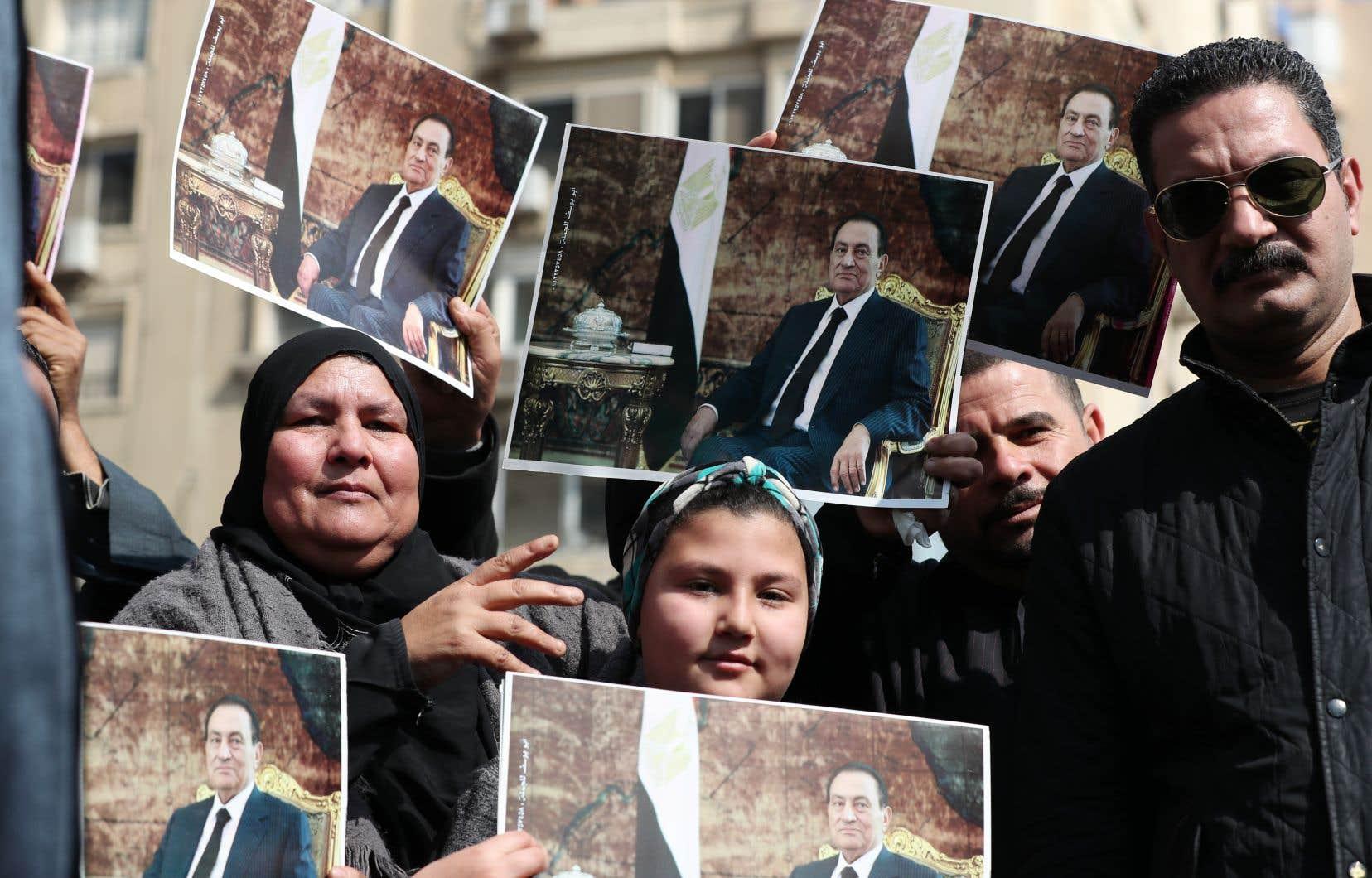Des partisans de l'ancien président égyptien Hosni Moubarak lui rendent hommage au lendemain de son décès, au Caire.