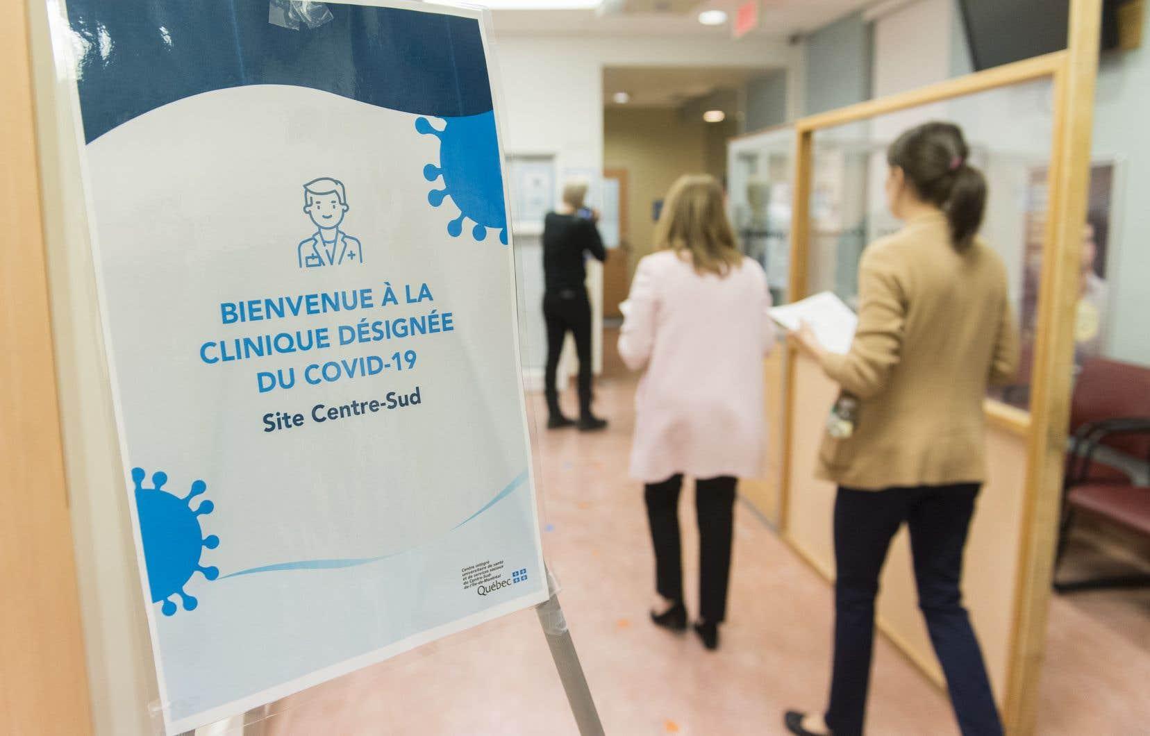Des gens passent devant un panneau lors d'une visite d'une clinique désignée d'évaluation de la COVID-19, à Montréal, le mardi 10 mars 2020.