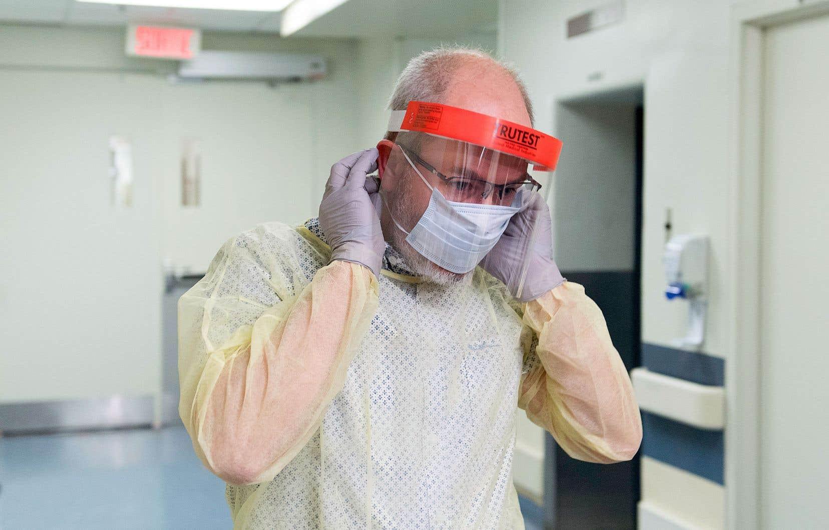 Un membre du personnel d'une des cliniques consacrées au dépistage du coronavirus montre comment bien mettre un masque médical.