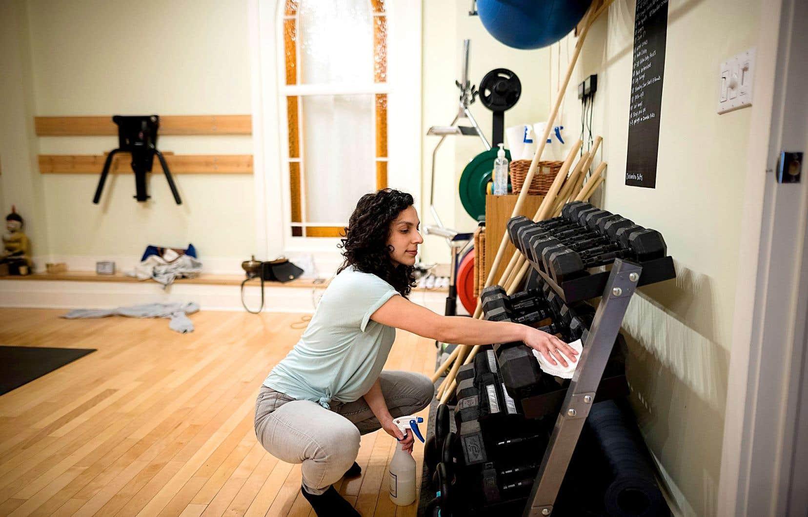 Une employée du gymnase Yogaspace a nettoyé avec assiduité les poids libres à la disposition des membres, mercredi.