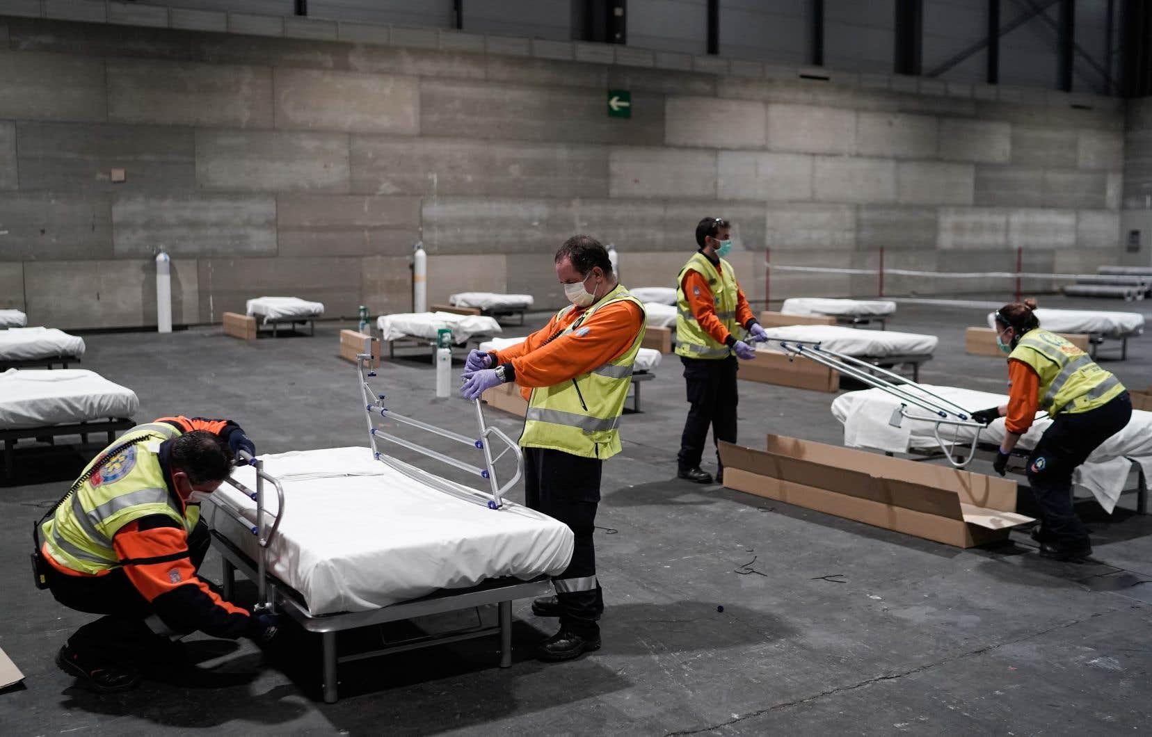 Des travailleurs installent des lits d'hôpital temporaires aménagés pour les patients atteints du coronavirus dans un pavillon du centre de conventions et d'expositions Ifema à Madrid, le 21 mars 2020.