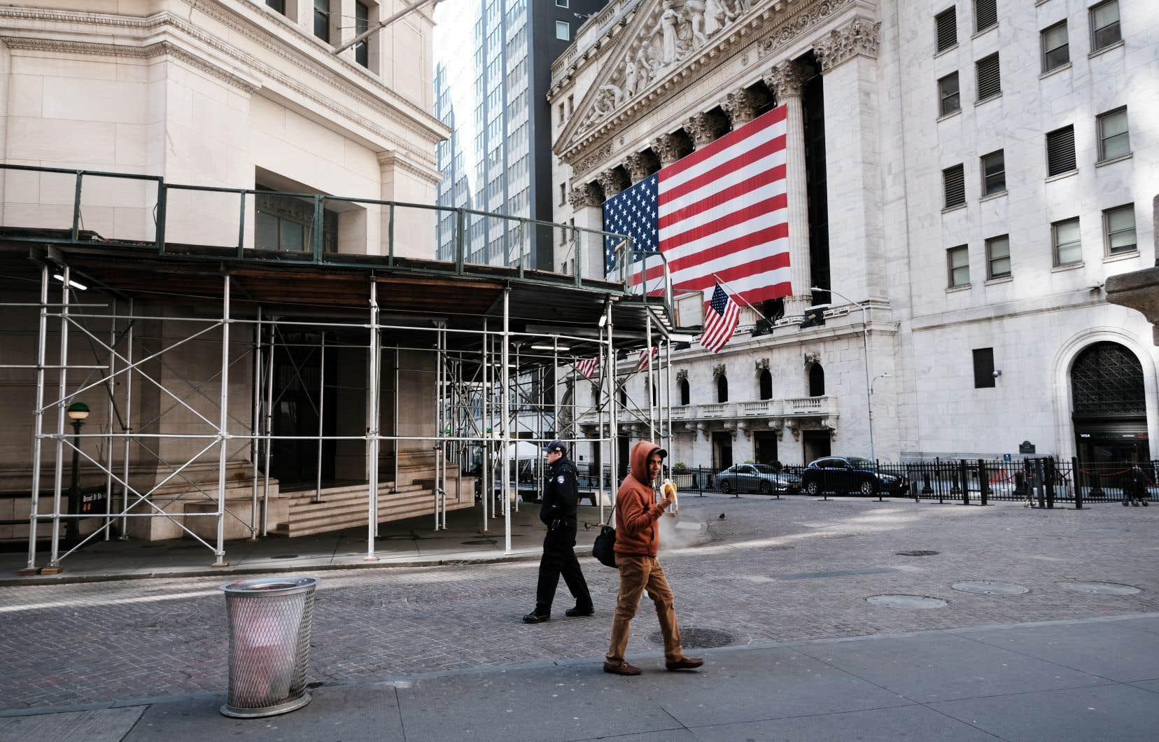 De rares marcheurs passaient devant la Bourse de New York, sur Wall Street, mardi.
