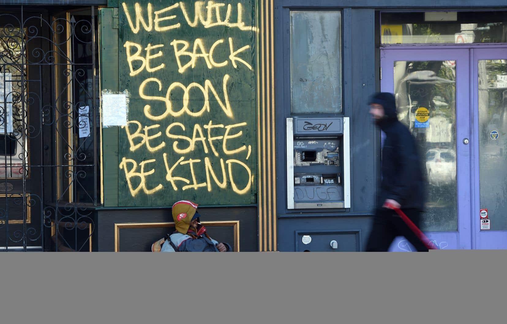 Un homme promène son chien devant un sans-abri dormant sous un message peint sur une boutique à San Francisco, en Californie.