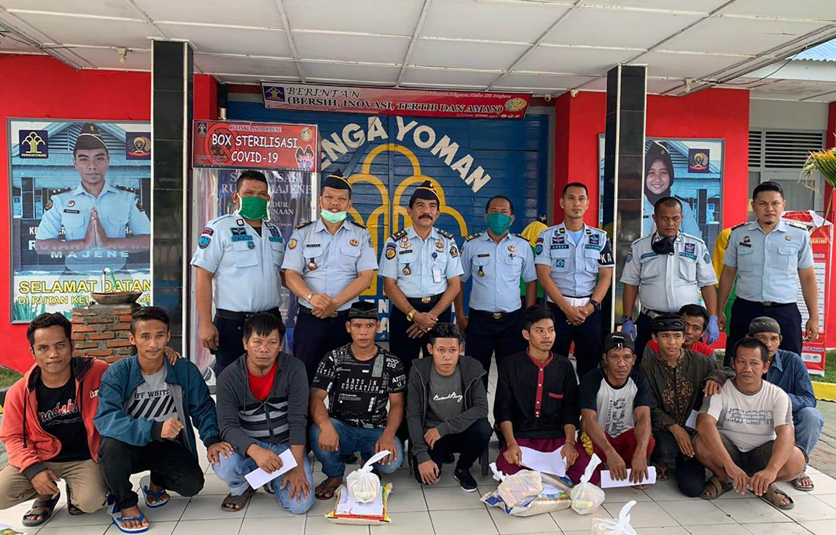 Des détenus (devant) posent pour une photo avec les responsables de la prison après leur libération.