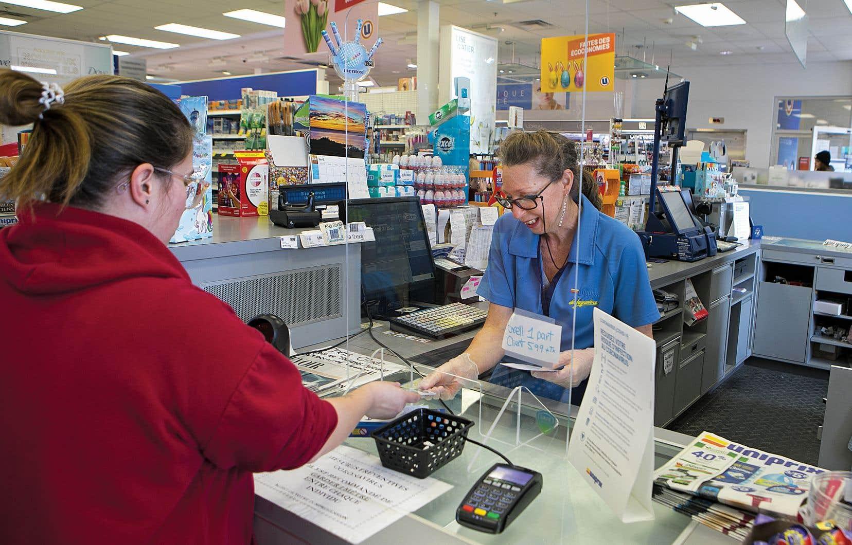 Un panneau en plexiglas et des gants en latex pour protéger la caissière de cette pharmacie