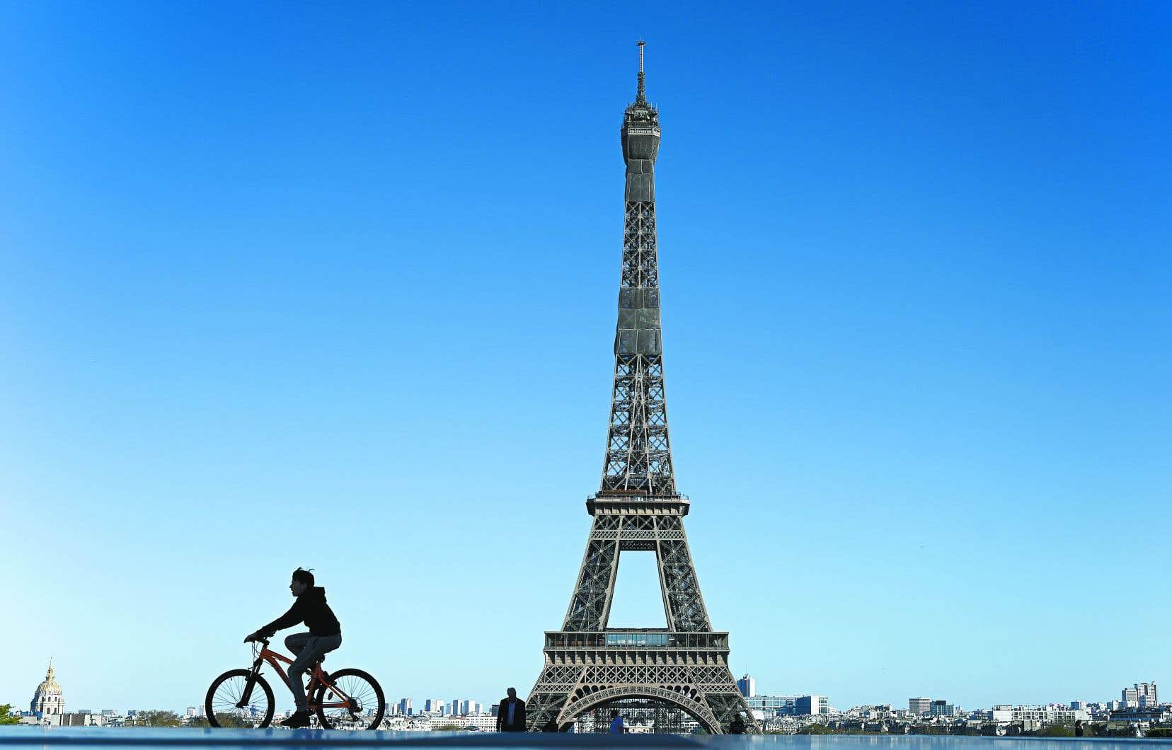 Un garçon passait à vélo devant la tour Eiffel à Paris, dimanche. 357 décès ont été enregistrés en France dimanche, soit le nombre le plus bas depuis une semaine, ce qui laisse présager un ralentissement de l'épidémie.