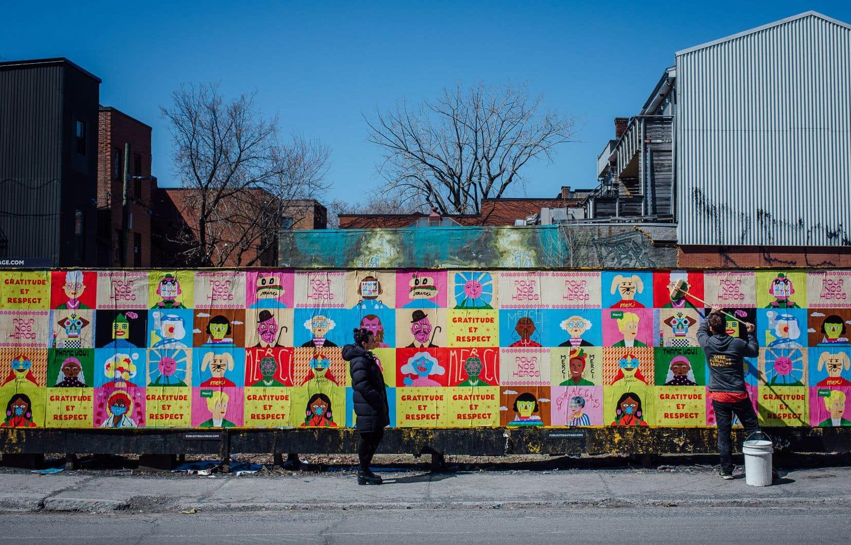 Benjamin Pommier, de Publicité sauvage, colle les affiches du projet Les couleurs essentielles sur une palissade, au coin de l'avenue des Pins et de la rue Saint-Denis.