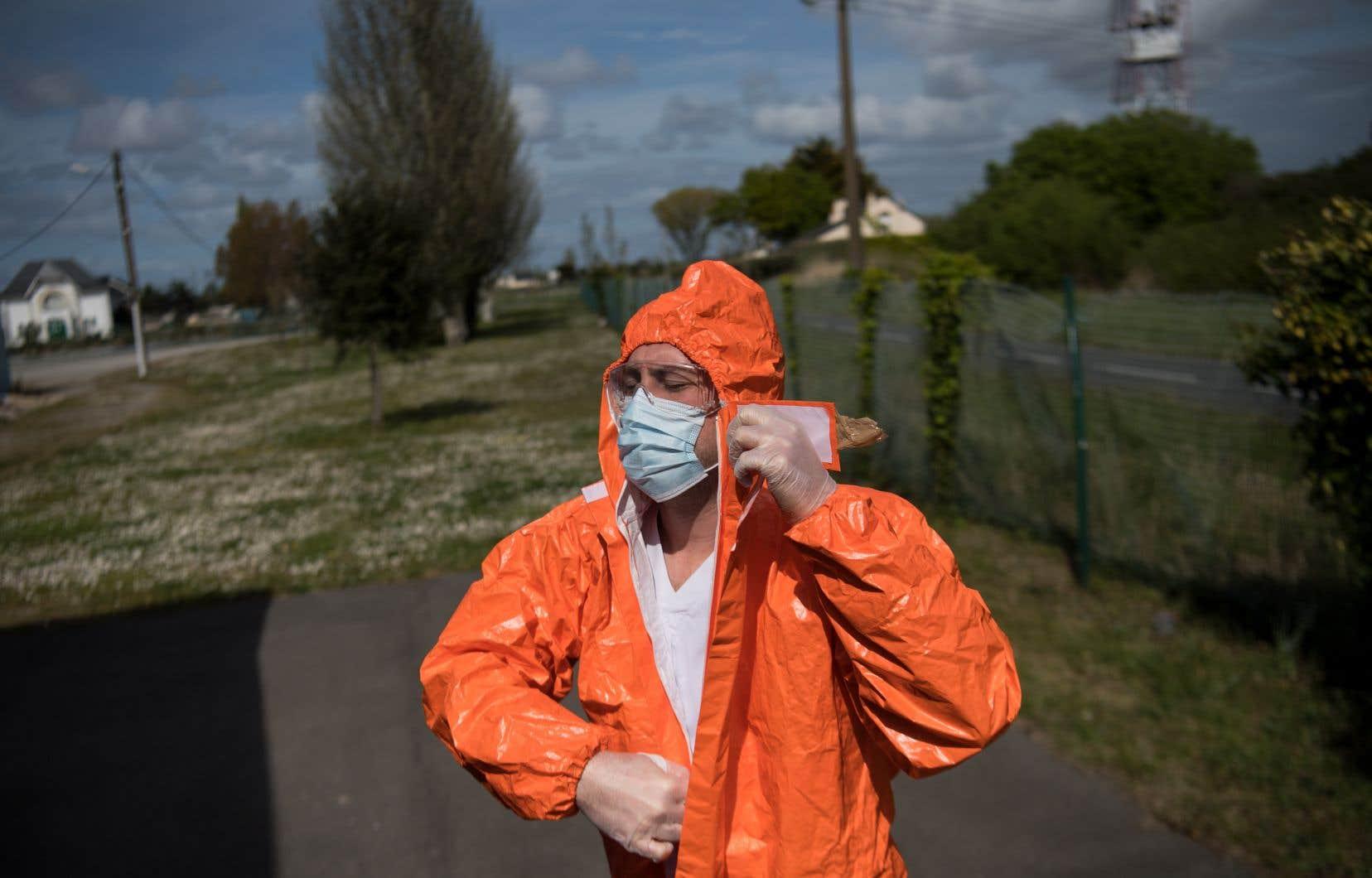 Un travailleur de la santé retirant son équipement de sécurité à Trignac, dans l'ouest de la France, lundi. L'Académie nationale de médecine préconise désormais la généralisation du port du masque au pays.