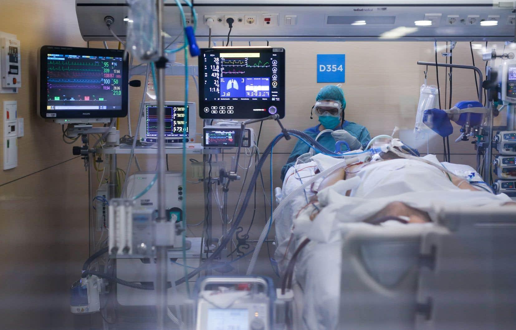 Le bilan quotidien de décès est reparti à la hausse en Espagne, mardi. Sur notre photo: un travailleur de la santé vêtu d'une combinaison prodiguait des soins à patient au département de soins intensifs de l'Hôpital Vall d'Hebron, à Barcelone, lundi.