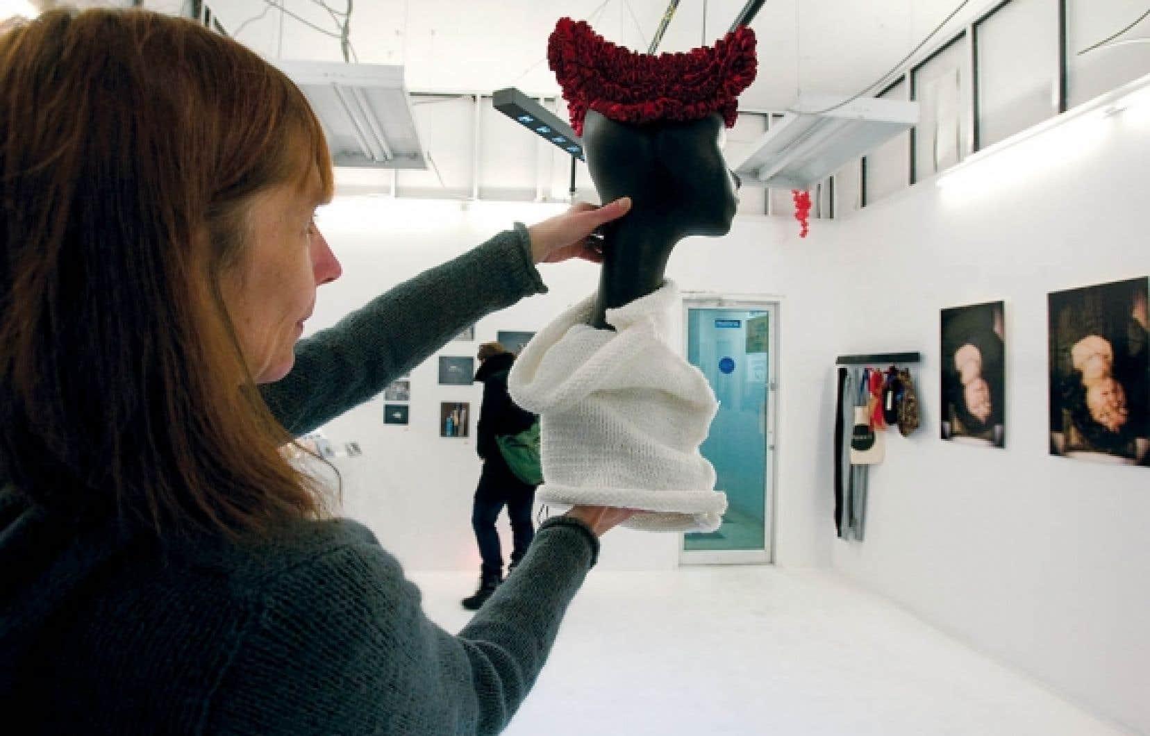 L'artiste fondatrice de l'Atelier Punkt, Melinda Pap, avec une de ses œuvres: un petit chapeau en ruban rouge plié, accompagné d'un cache-cou de la série -45C du studio Rita.<br />