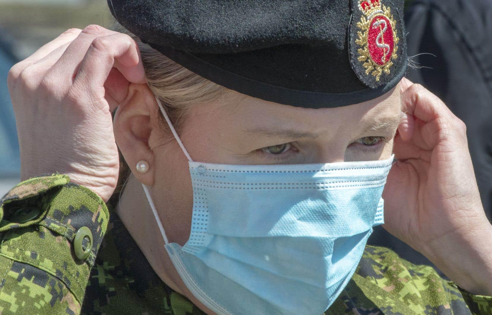 Une membre des Forces armées canadiennes dépêchée au CHSLD Villa Val des Arbres, à Laval, ajuste son masque avant d'entrer dans la résidence.