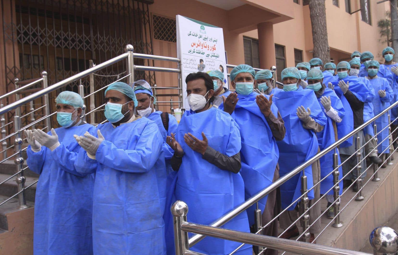 Des membres du personnel soignant d'un hôpital à Quetta, au Pakistan, prient avant l'amorce de leur quart de travail en fin mars 2020.