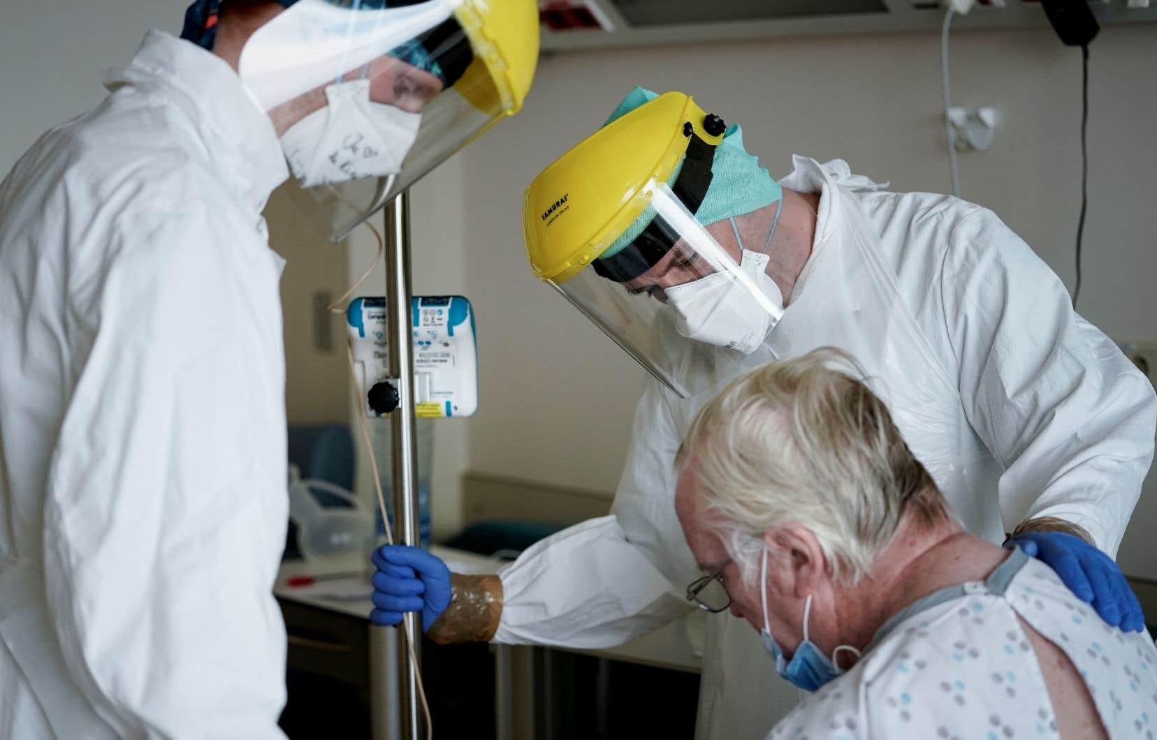 Des membres du personnel médical rendent visite à un patient atteint de la COVID-10 à l'hôpital Erasme, à Bruxelles. Parmi les pays les plus durement touchés, la Belgique est celui qui déplore le plus grand nombre de morts par rapport à sa population.