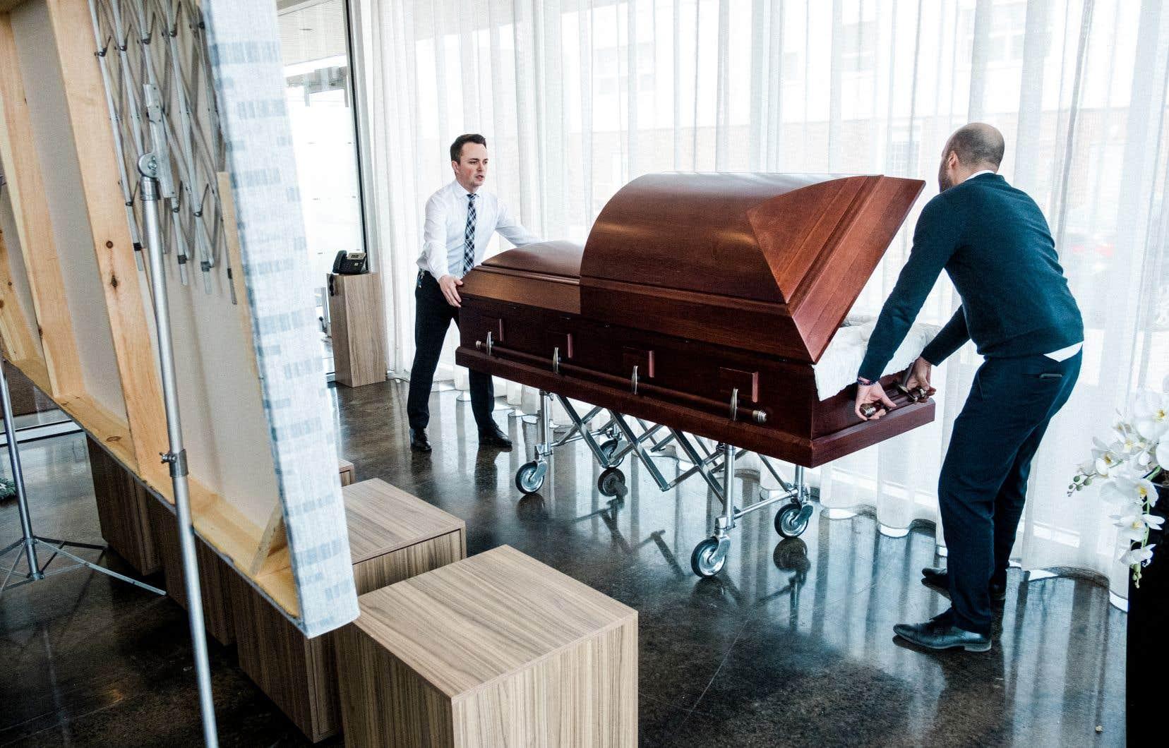 Les employés du salon funéraire préparent la présentation, qui se fera pour une toute première fois au travers d'une vitrine. Les visiteurs arrivent en voiture de façon à pouvoir rassembler plus de 10 personnes.