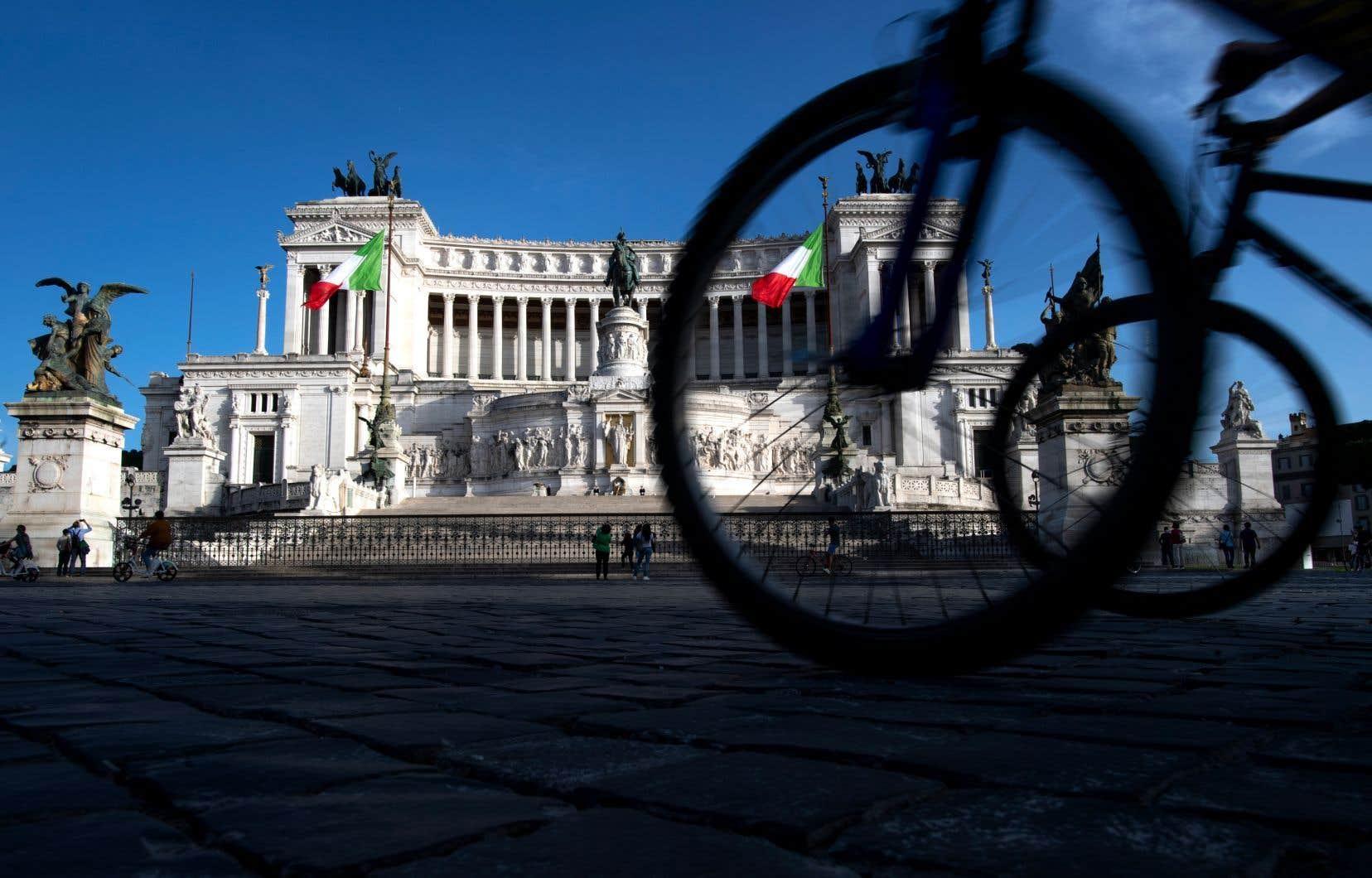 Des gens circulent à vélo devant le monument de l'Altare della Patria dans le centre de Rome le 10 mai 2020.
