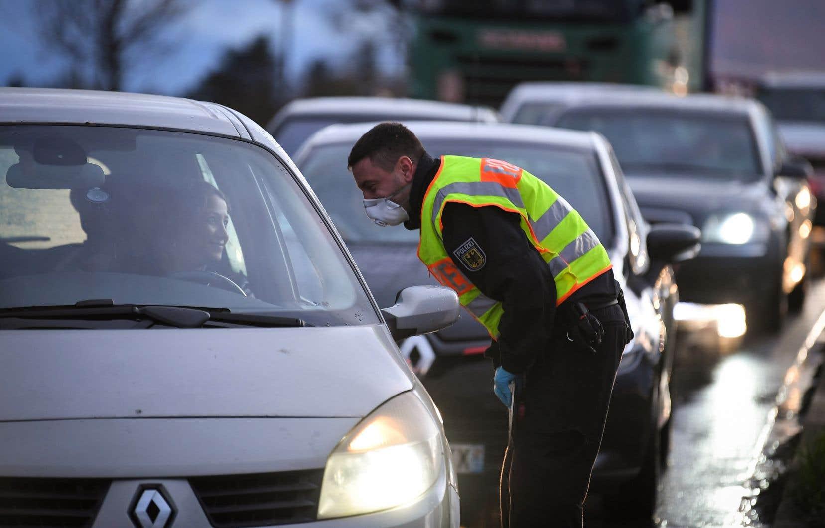 Un policier allemand contrôle des passagers entrant traversant la frontière avec la France, avant la fermeture de celle-ci en mars.