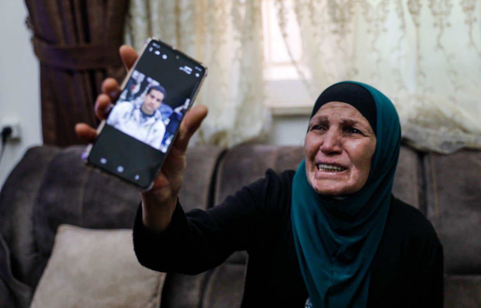 La mère d'Iyad Kheiri Hallak, un Palestinien du quartier de Wadi Joz, à Jérusalem-Est, pleure son fils en montrant sa photo.
