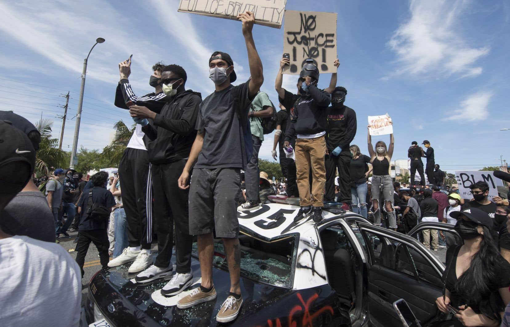 Des manifestants se tiennent debout sur une voiture de police vandalisée pour protester contre la violence policière à Los Angeles, samedi.