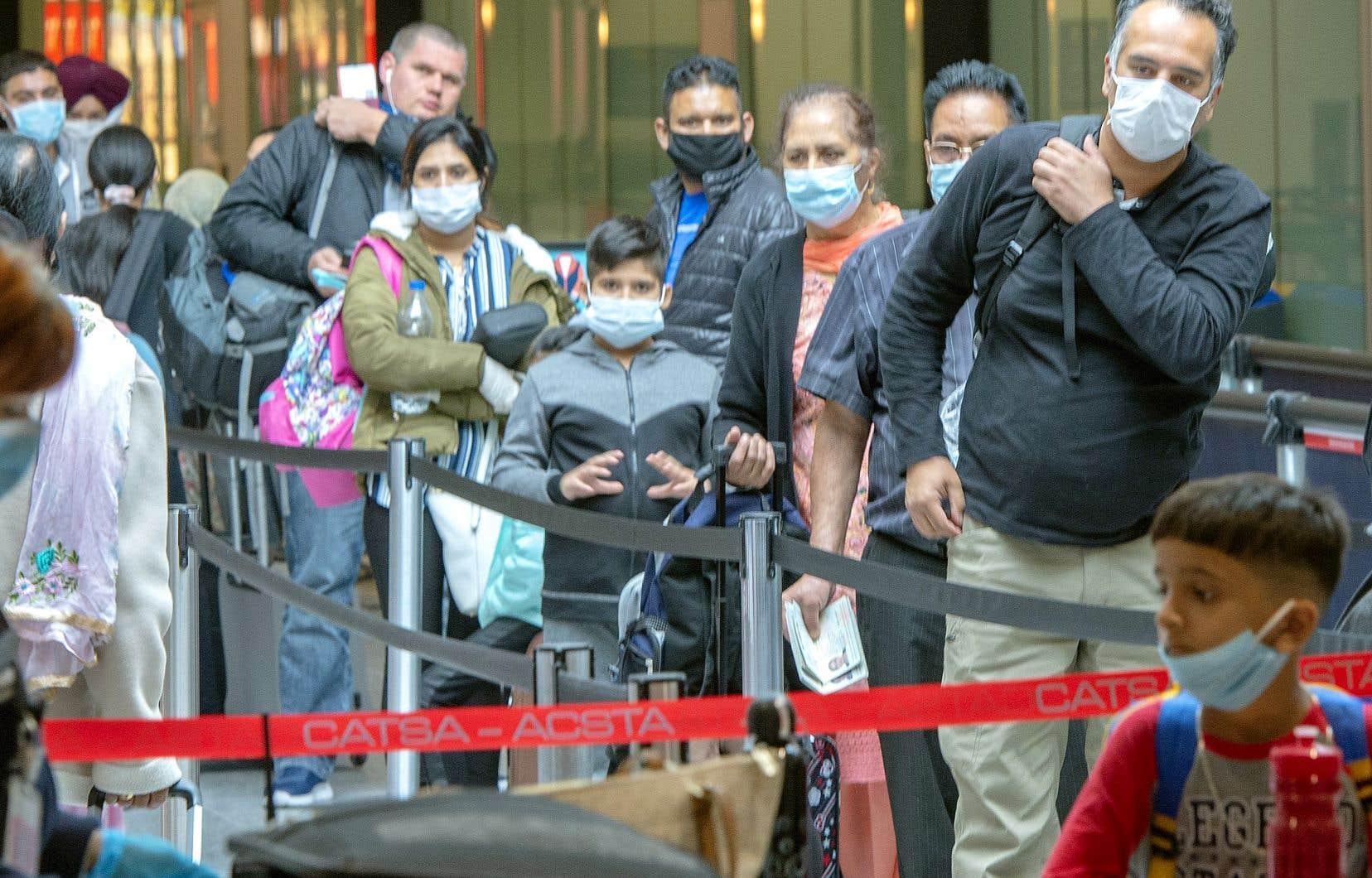 Des passagers portant un masque obligatoire à l'aéroport Montréal-Trudeau