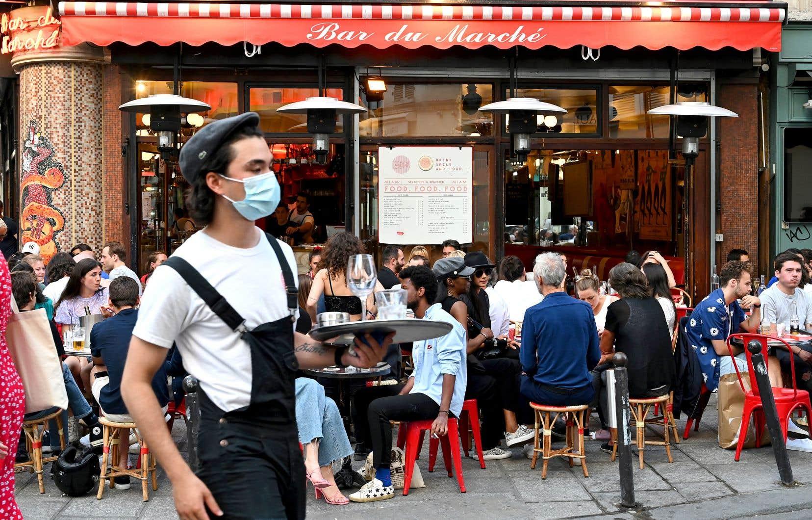 Si le reste du pays voit ses bars et restaurants rouvrir leurs salles, à Paris, en «zone orange», seules les terrasses peuvent accueillir la clientèle. Sur cette photo, un serveur porte le masque en passant entre les tables bondées, une mesure désormais obligatoire.
